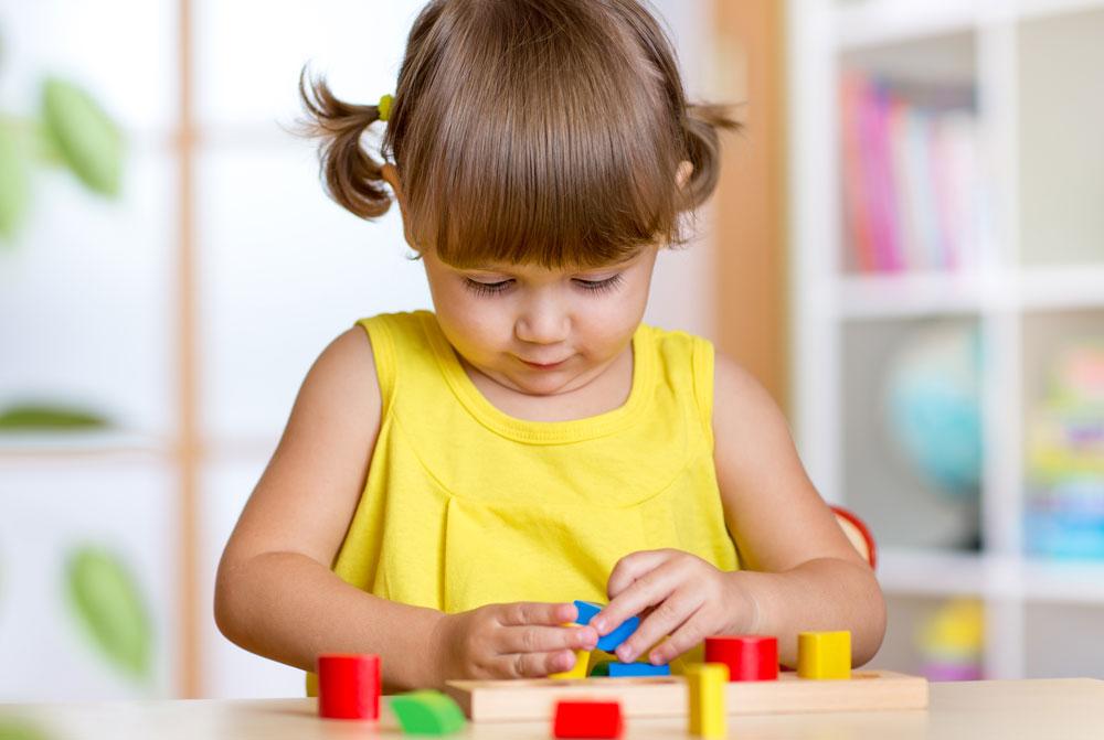Kind spielt mit Holzspielzeug im Rahmen einer ergotherapeutischen Sitzung